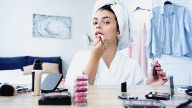 Yatak odasında dekoratif kozmetik ürünlerle makyaj masasının yanında ruj süren genç bir kadın.