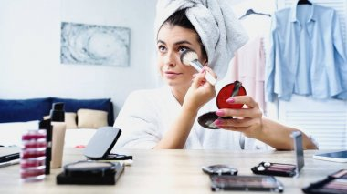 Young woman in bathrobe with head wrapped in towel applying face powder with cosmetic brush in bedroom stock vector