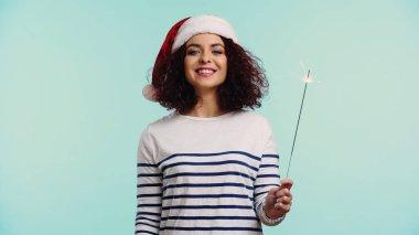Noel Baba şapkalı, elinde maytap tutan mutlu genç kadın mavi üzerinde izole edilmiş.