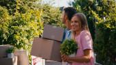 boldog férj és feleség séta kartondobozokkal és növényekkel, áthelyezési koncepció