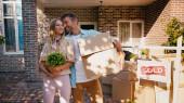 boldog férfi ölelés nő növény áll közel az új ház