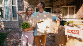 glückliches Paar mit Kästen und Pflanzen, die in der Nähe des neuen Hauses stehen