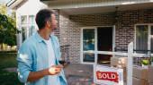 freudiger Mann hält ein Glas Rotwein in der Hand und blickt auf das neue Haus