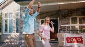 boldog férfi kezében kulcsok közelében feleség és tánc közelében új ház és eladott ellátás