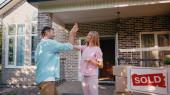 glückliches Paar gibt High Five in der Nähe von neuem Haus und verkaufte Vorstand