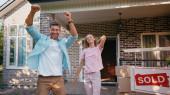 Aufgeregter Mann freut sich über Frau, neues Haus und verkaufte Tafel