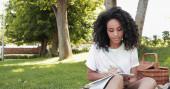 kudrnaté africké americká žena psaní v notebooku v parku