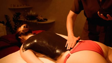masseur applying mud on body of woman on massage table in wellness center