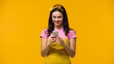 Pretty smiling woman using mobile phone isolated on yellow