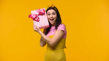 Astonished woman holding gift near ear isolated on yellow