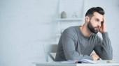 vousatý a stresovaný muž dívá pryč kalkulačka na stole