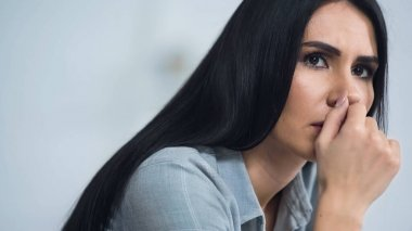 worried woman biting nail and looking away at home
