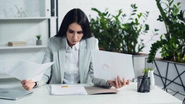 displeased businesswoman looking at documents in office