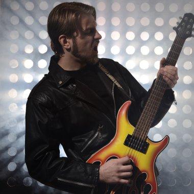 rock guitarist playing electric guitar in fog