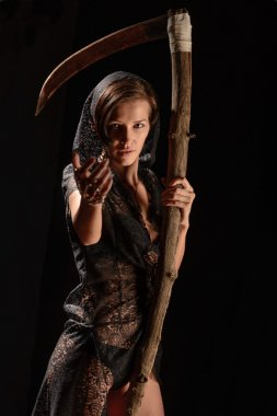 Girl in a black lace smock with scythe of death.