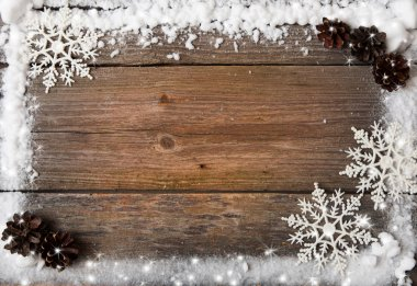 A snow frame with snowflakes and cones over wooden background, copy space stock vector