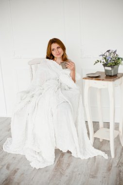 beautiful women with morning coffee sitting in white chair