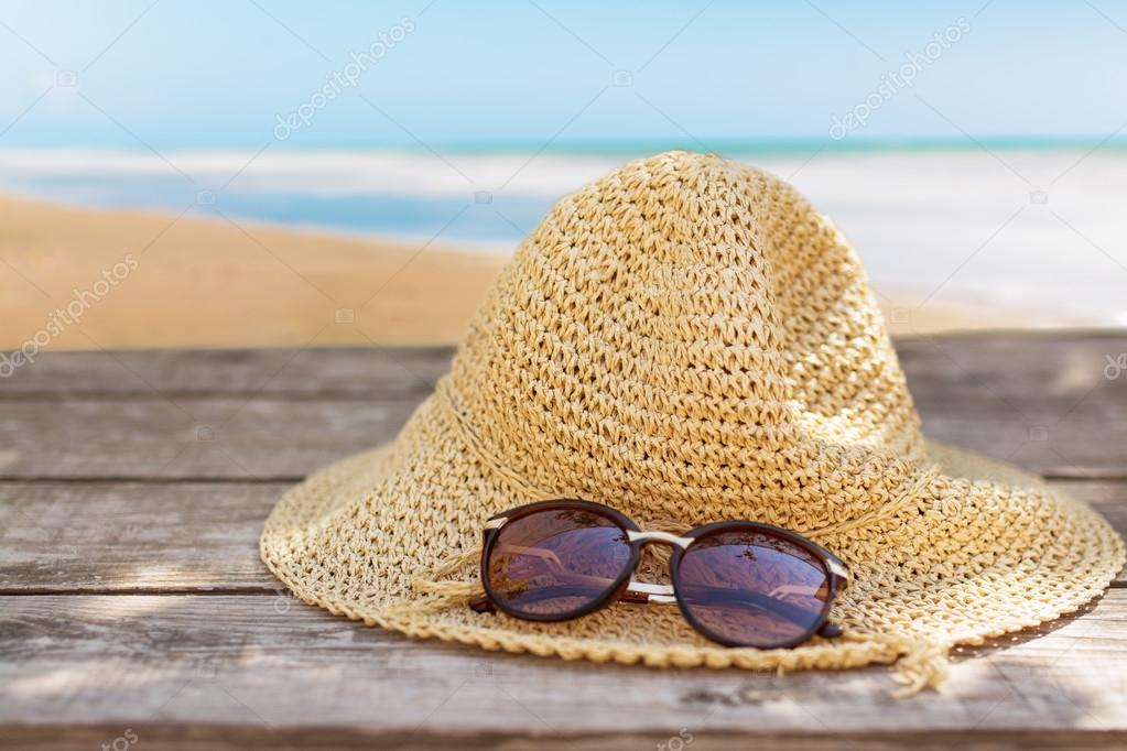 fedora hat and sunglasses over wooden table and sea landscape background.