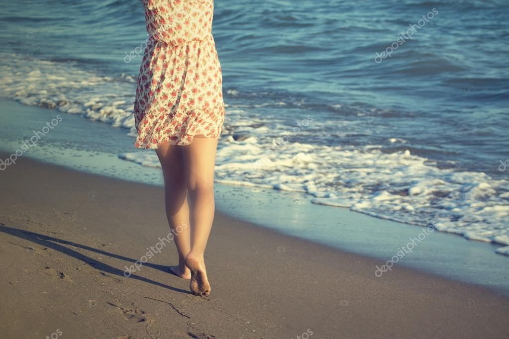 The legs of a woman walking on a beach