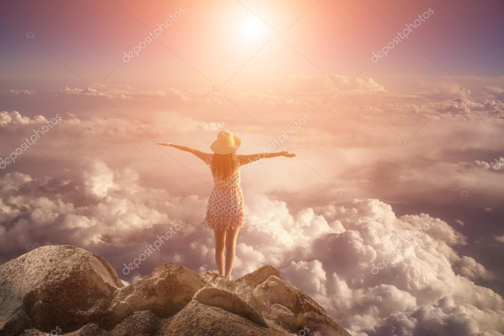 freedom young  woman jumping on mountain peak rock