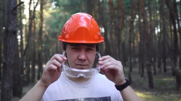 Bauarbeiter mit Helm setzt Brille auf