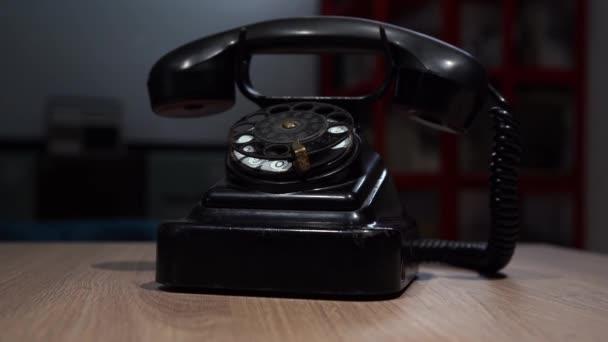 altes sowjetisches Telefon schwarzer Farbe steht auf einem Holztisch