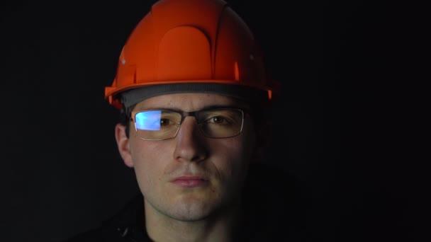 ein Mann mit Brille und Helm, der auf dunklem Hintergrund in die Kamera blickt