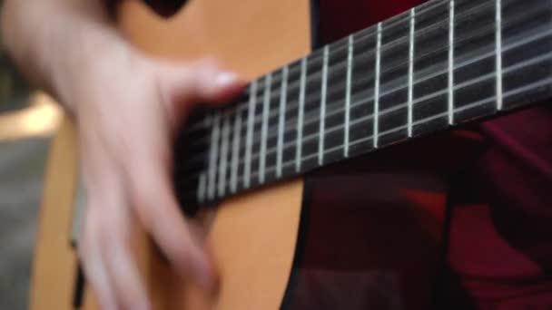 muž hraje na kytaru, zatímco sedí na ulici