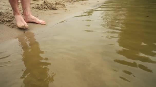 mans feet entering the river along the sandy beach close-up