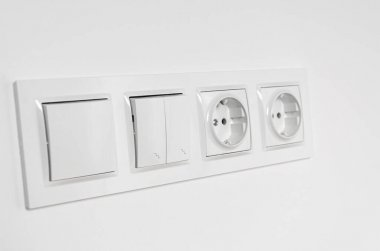 White plastic walk-through switches and sockets on a white wall. Repairs