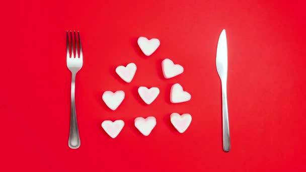 Romantický nápad na valentýnskou večeři. Srdce na talíři a stříbro na červeném pozadí. Zastavit animaci pohybu.
