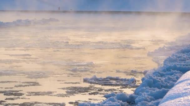 Schmelzendes rissiges Eis fließt an einem nebligen Morgen den Fluss hinunter. Neblige Wasseroberfläche am Ende des Winters. Eisdrift.