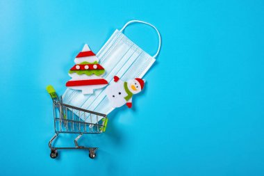 Shopping cart with medical mask and Christmas decorations on blue background stock vector
