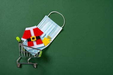 Shopping cart with medical mask and Christmas decorations on green background stock vector