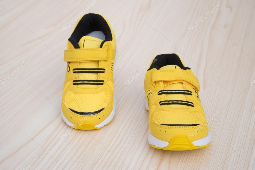 e53a39fa8b Par de zapatillas deportivas amarillas para niños sobre un fondo de madera  — Foto de Stock
