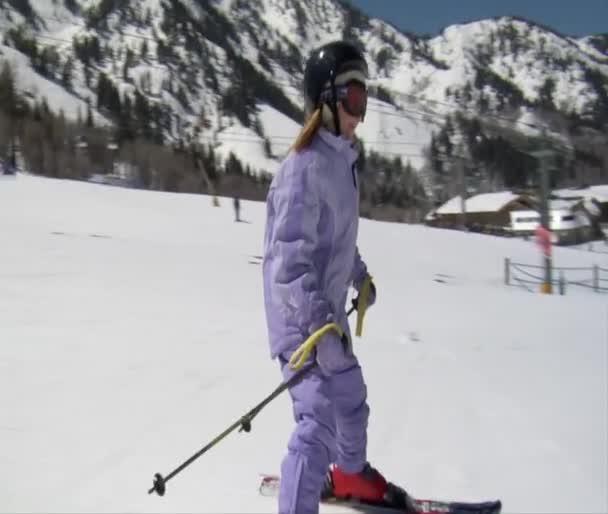 Lyžař na sobě světle fialovou kombinézu