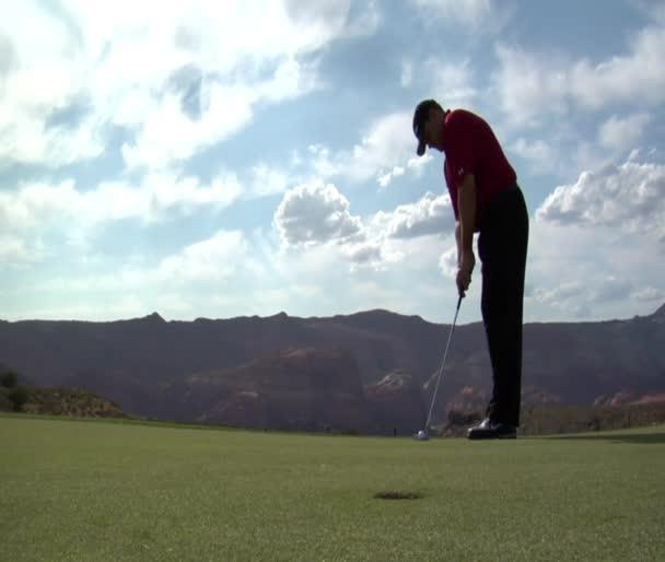 Člověk klade golfový míček do díry