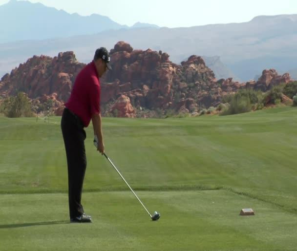 Man auf rotem Gestein Golfplatz abschlagen