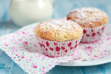 Close-up of two homemade lemon muffins with a jug of milk, selec