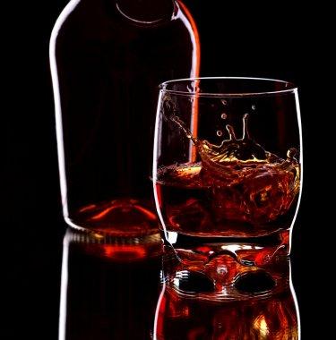 Glass and bottle of whiskey with splash on dark background, sele