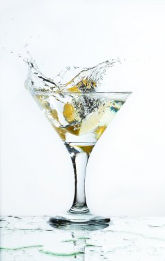 A glass of martini and slice of lemon, a splash and spray on a l