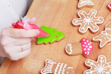 Decorating gingerbread cookies (Christmas tree) with red icing,