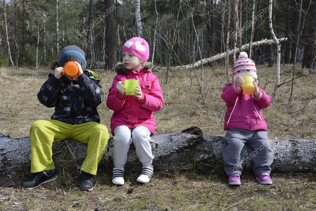 Spring in the woods sitting on a log and small children drink te