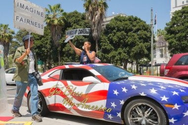 People holding sign next to a car painted in american flag color