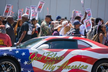 Car painted with american flag colors in front of protestors