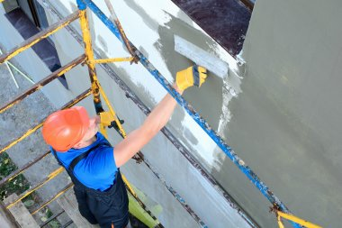 Worker spreading mortar over styrofoam insulation stock vector