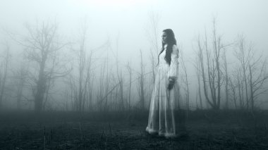 Horror woman in the foggy forest