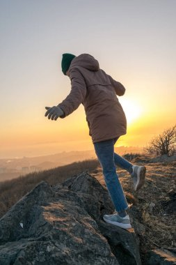 Girl in a jacket and a hat on the mountain during sunset