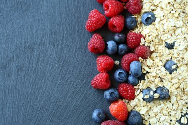 Healthy breakfast and berries on slate background