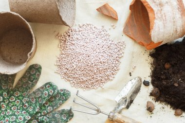 Heap of mineral fertilizers among garden tools. Concept with pots, earth, glove, scoop.